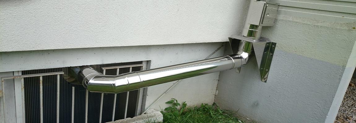 Abgasleitung - An ein Blockheizkraftwerk installierte Abgasleitung. Die Leitung wurde aus Fertigteilelementen dem konkreten Gebäudeumriss passend zusammengesetzt.